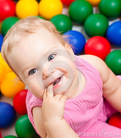 Smiling infant playing among colorful balls