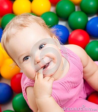 Smiling infant playing among colorful balls