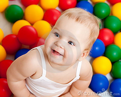 Smiling infant sitting among colorful balls