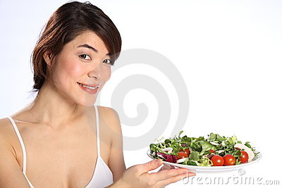 Smiling Japanese girl holds out plate green salad