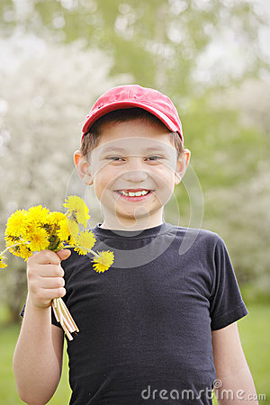 Smiling kid with dandelions