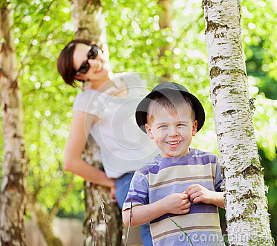Smiling kid and his mom in the background