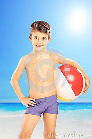 Smiling kid in swimming shorts, holding a beach ball and posing
