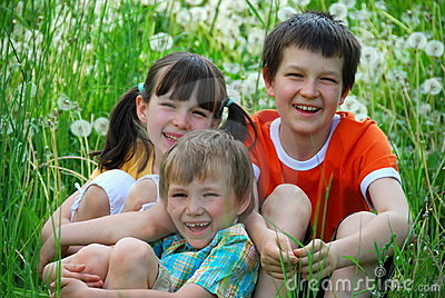 Smiling kids in grassy field