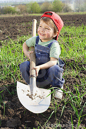 Smiling little boy with big shovel