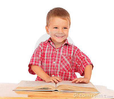 Smiling little boy reading book on the desk