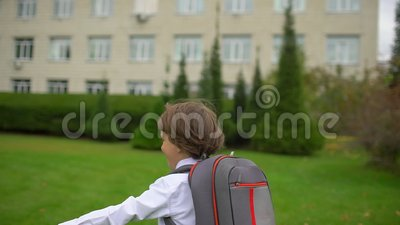 Smiling little boy schoolboy student with backpack going and running to school outdoors, First-grade student, primary. Smiling little boy schoolboy student with stock video footage