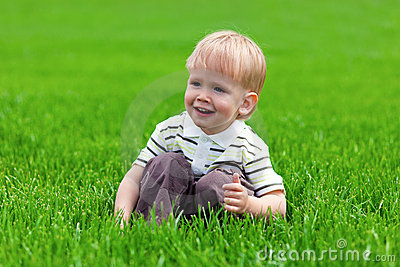 Smiling little boy sitting in fresh grass