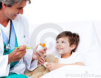 Smiling little boy taking cough medicine
