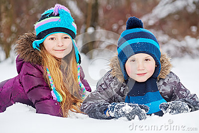 Smiling little girl and boy lie side by side on snowdrift