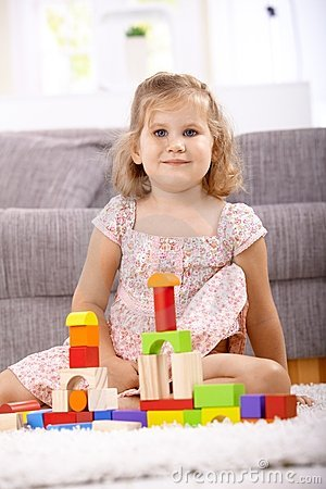 Smiling little girl building tower at home