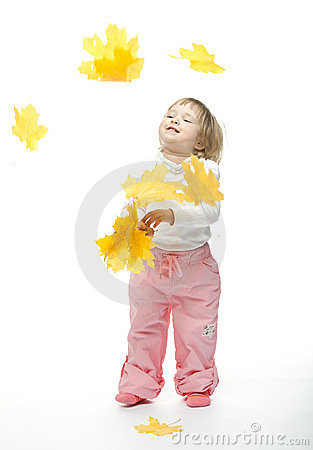 The smiling little girl catching yellow leaves
