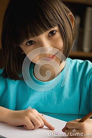 Smiling little girl  draws.
