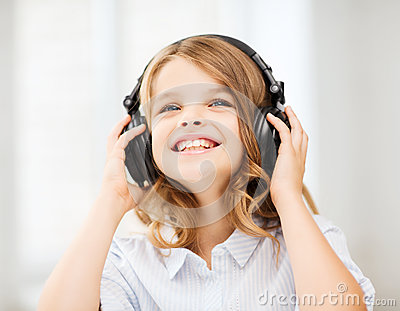 Smiling little girl with headphones at home