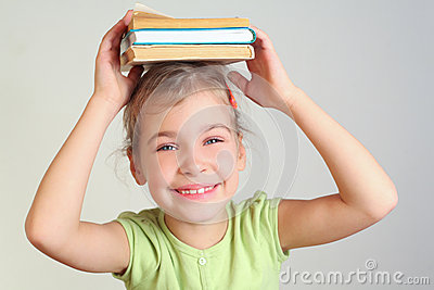 Smiling little girl hold books