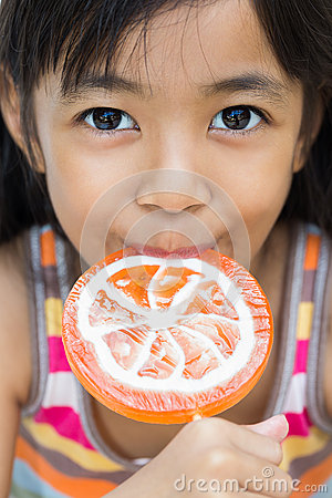 Smiling little girl with a lollipop