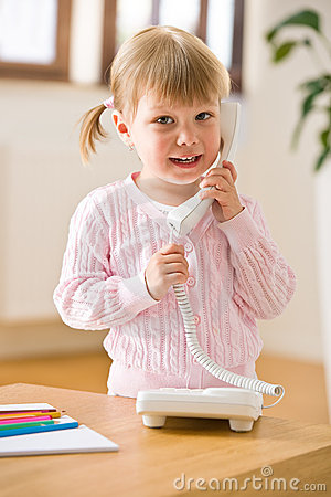 Smiling little girl on phone in lounge