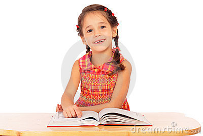 Smiling little girl reading book on the desk