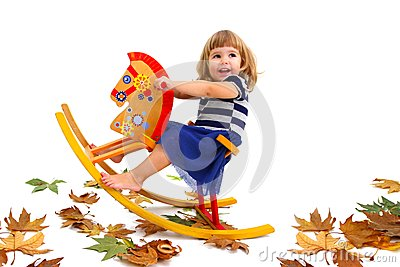 A smiling little girl riding a wooden horse
