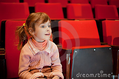 Smiling little girl sitting on armchairs at cinema