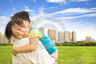 Smiling little girl sleeping on  father shoulder at city park
