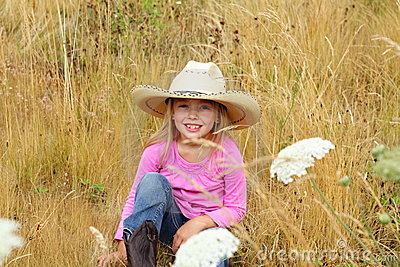 Smiling little girl wearing large hat.