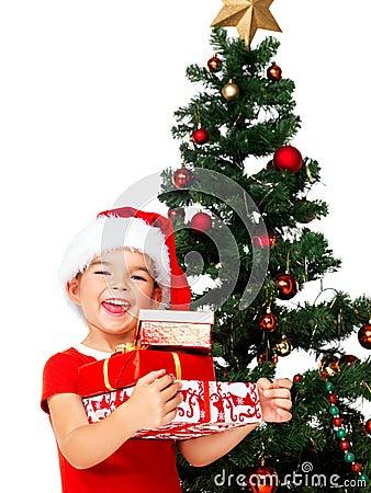 Smiling little Santa girl holding gift boxes
