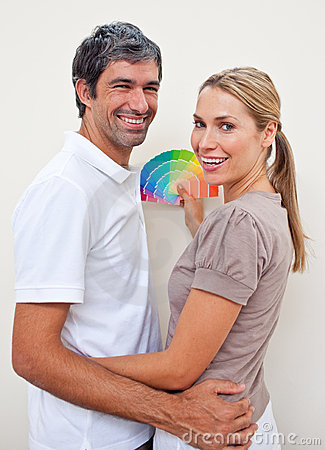 Smiling lovers with color samples to paint