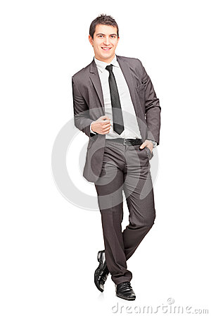 Smiling male businessman leaning against wall