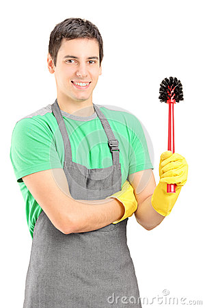 A smiling male cleaner holding a toilet broom