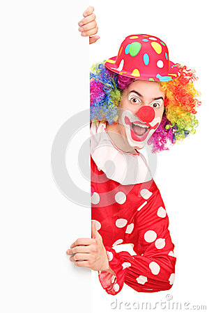 A smiling male clown posing behind a panel