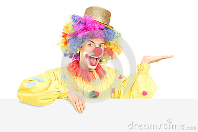 Smiling male clown standing behind blank panel gesturing with ha