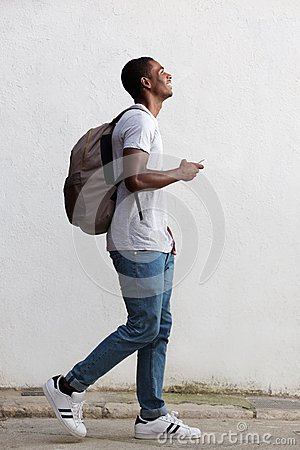 Free Smiling Male College Student Walking With Bag And Mobile Phone Royalty Free Stock Image - 56495316