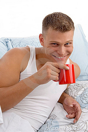 Smiling male drinking coffee in bed