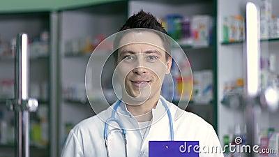Smiling male pharmacist in white coat in drugstore stock video