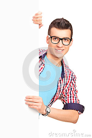 A smiling male posing behind a white panel