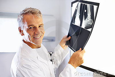 Smiling male radiologist examines x-ray