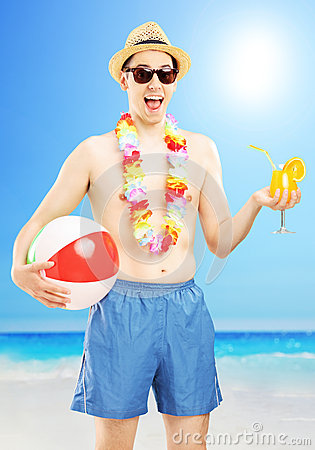 Smiling male in swimming shorts, holding a ball and cocktail