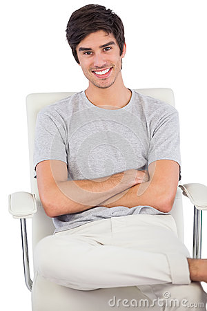 Smiling man with arms crossed sitting on a swivel chair