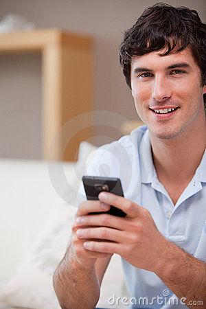 Smiling man with cellphone in his hands