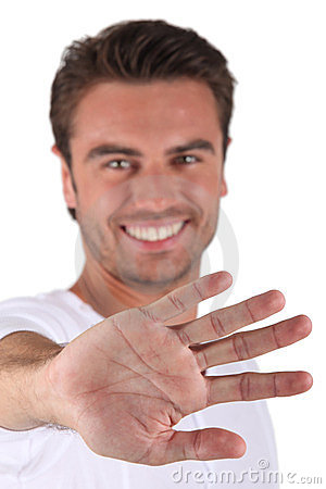 Smiling man displaying palm