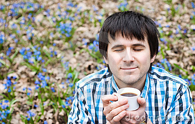 Smiling man drinking coffee in  wood