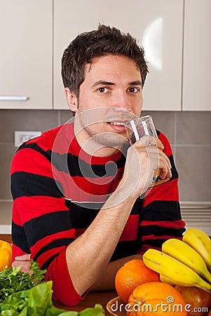 Smiling man drinking fresh orange juice