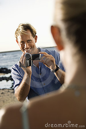 Smiling Man Filming Woman At Beach