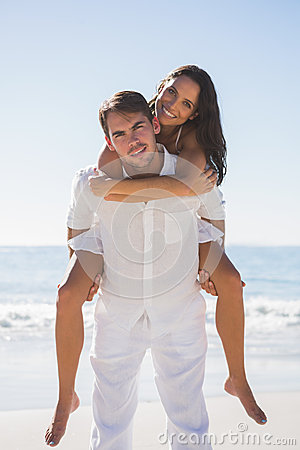 Smiling man giving happy girlfriend a piggy back looking at came