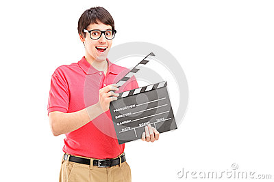 A smiling man with glasses holding a movie clap