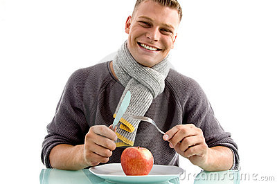 smiling man going to eat apple with fork and knife stock