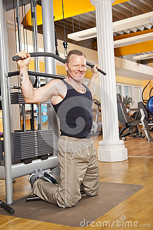 Smiling man in his forties exercising in gym