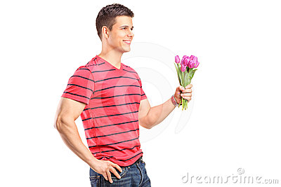A smiling man holding a bunch of flowers