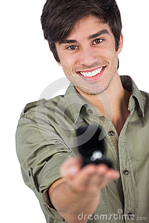 Smiling man holding engagement ring